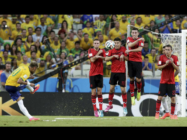 Brazil's Neymar, left, takes a free kick against Mexico's defensive wall