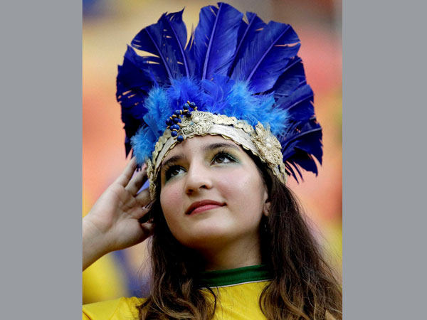 A spectator adjusts her headdress before the start of the group A World Cup