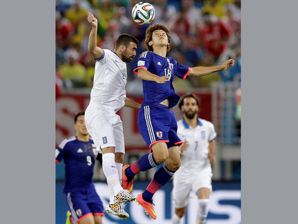 Japan's Yuya Osako, right, is challenged for a high ball