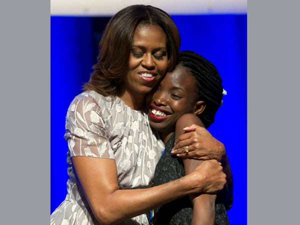 First lady Michelle Obama hugs graduate Faith Ajayi after she was presented with a Student Achievement Award during the DC College Access Program Class of 2014 graduation in Washington