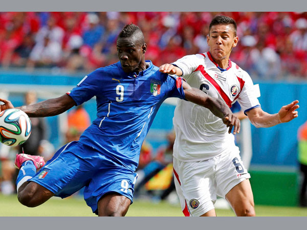 Italy's Mario Balotelli, left, gets in a shot despite the challenge