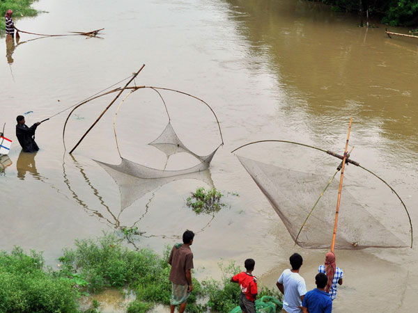 People use Chinese nets as they fish in a river of Agartala