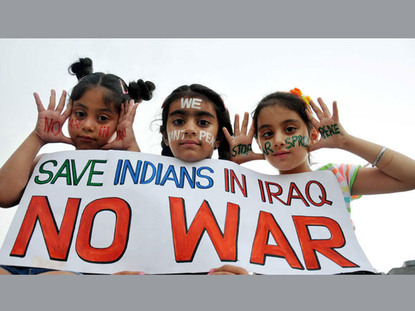 Children hold a placard reading 'Save Indians in Iraq - No War'