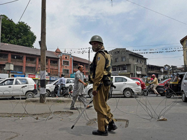 A security jawan patrols during a strike call given by JKLF