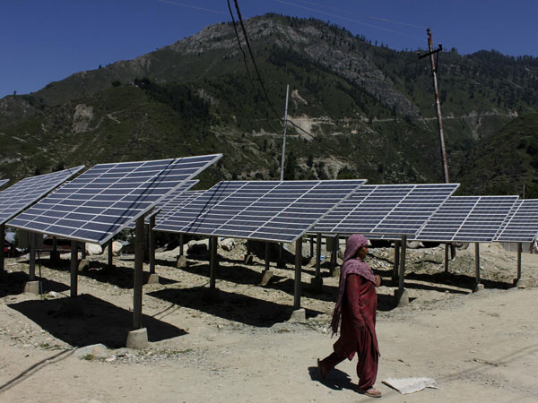 A woman walks past defunct solar panels installed