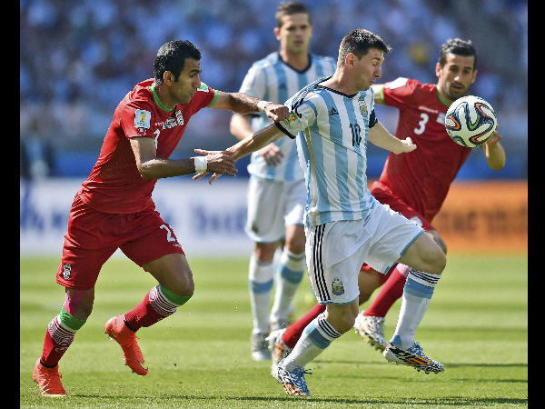 Iran's Mehrdad Pooladi, left, holds Argentina's Lionel Messi during the Group F World Cup match between Argentina and Iran at the Mineirao Stadium in Belo Horizonte, Brazil, Saturday, June 21.