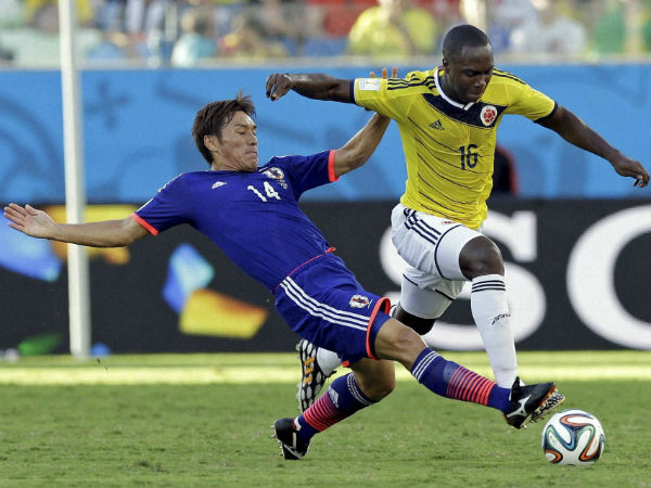 Japan's Toshihiro Aoyama, left, challenges Colombia's Eder Balanta during the group C World Cup soccer match between Japan and Colombia at the Arena Pantanal in Cuiaba, Brazil, Tuesday, June 24. Colombia won 4-1.