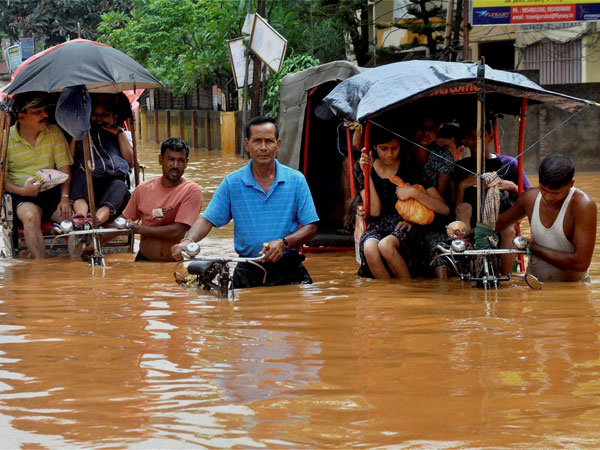 Rickshaw pullers wade through a waterlogged street