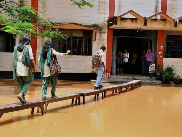 Students using benches to enter their school inundated