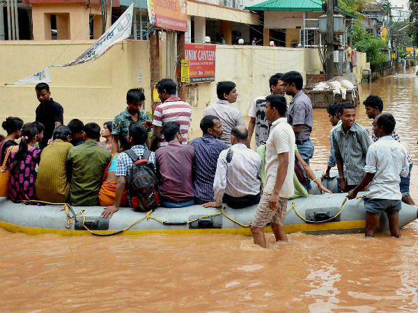 People use rubber boats provided by the district administration to commute in the waterlogged Rajgarh area after heavy rains in Guwahati on Friday. (PTI photo)