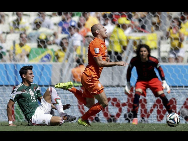 Netherlands' Arjen Robben, right, goes down under a challenge from Mexico's Hector Moreno