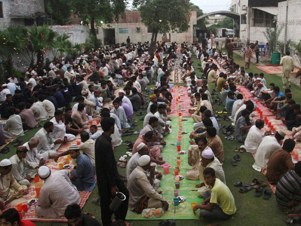Pakistani Muslims wait to break their fast at sunset