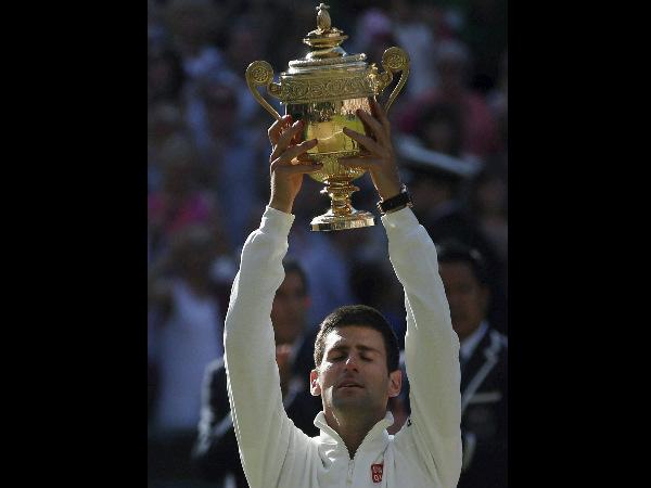 Novak Djokovic holds up the trophy after defeating Roger Federer