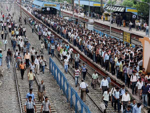 commuters walk at platform and tracks at a railway station