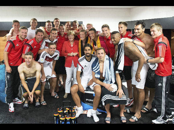 The photo provided German government shows German Chancellor Angela Merkel, center, posing for a photo with the German national soccer team after Germany won 4-0 in the group G World Cup soccer match between Germany and Portugal at the Arena Fonte Nova in Salvador, Brazil, Monday, June 16, 2014. Merkel will be at the stadium for the final.