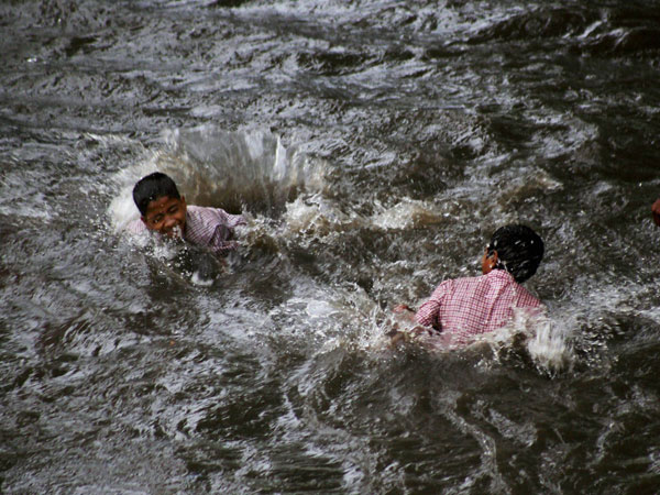 Children playing at a waterlogged road after heavy rains