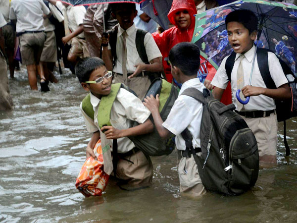 School children wading through a waterlogged street