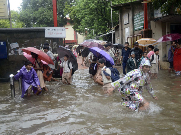 School students play on a waterlogged streets of Mumbai