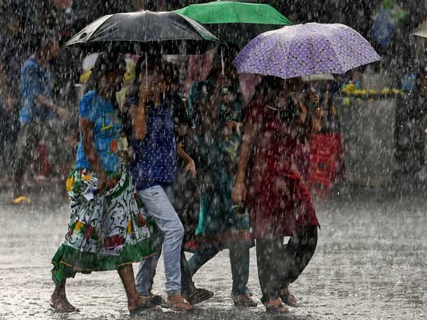 Young walk with umbrellas as it rains in Kolkata