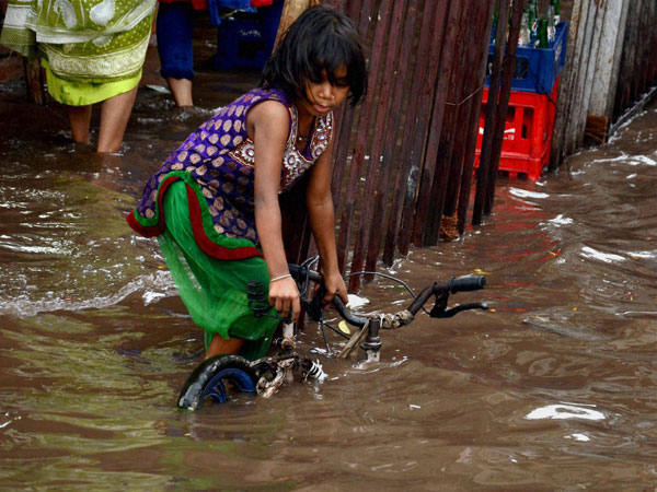 A girl trying to pull her bicycle from a waterlogged road