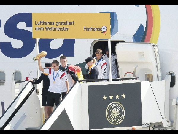 German captain Philipp Lahm with the World Cup trophy, Sebastian Schweinsteiger, Thomas Muller and Sami Khedira, from left arrive at Tegel airport in Berlin Tuesday, July 15, 2014.