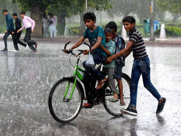 Children riding bicycle during rain near India Gate