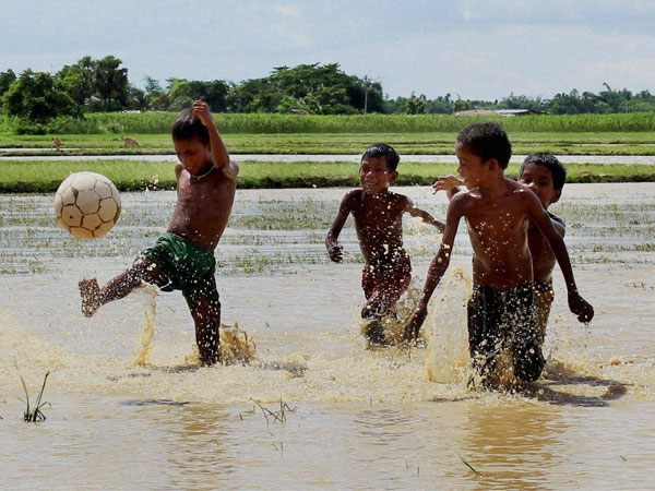 Children playing football in a waterlogged field
