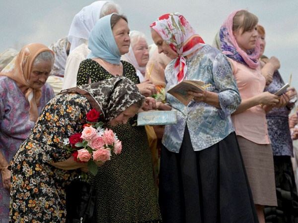 A women bows during a religious service held by villagers