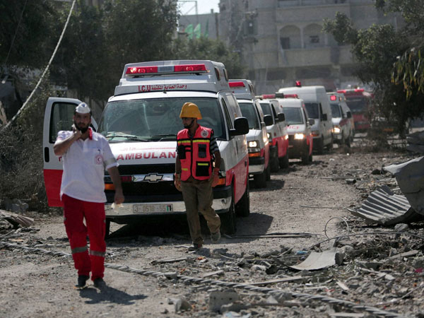 A Palestinian rescue convoy navigates rubble in Gaza City