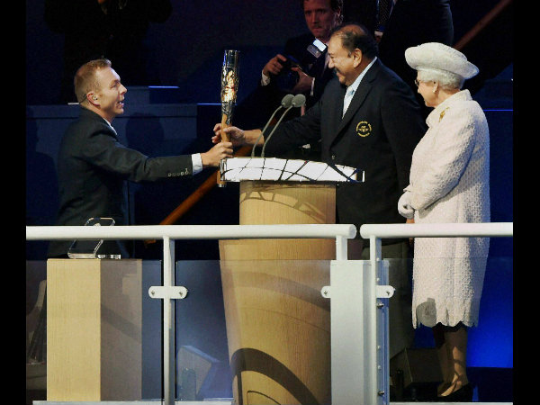 Britain's Queen Elizabeth II looks on as Sir Chris Hoy hands over baton to CGF president Prince Imran at Celtic Park during the opening ceremony of Commonwealth Games in Glasgow, Scotland on Wednesday (July 23)