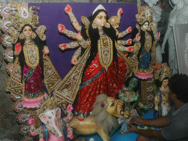 Subol Paul, an artist gives finishing touches to an idol of goddess Durga