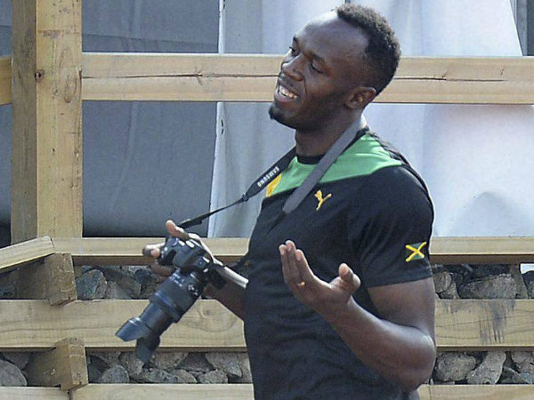Usain Bolt holds a camera during a training session at the warm up track next to Hampden Park, during the Commonwealth Games in Glasgow on Wednesday (July 30).