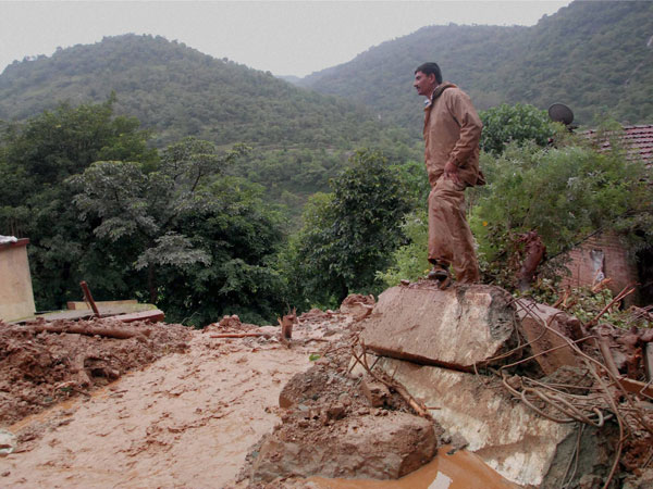 A rescuer looks at the debris at the site of a landslide