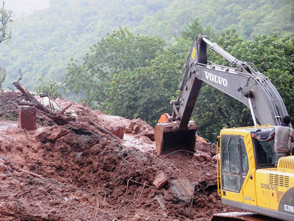 Rescue workers clear the debris at the site of landslide
