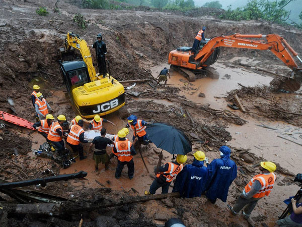 Rescue workers clear the debris at the site of a landslide