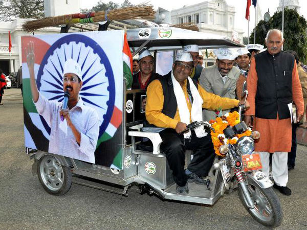 AAP leaders sitting in an e-rickshaw during poll campaign.
