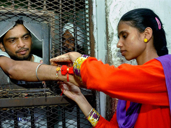 A girl ties a rakhi to her prisoner brother at the Patiala