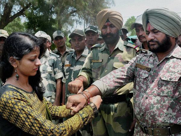 A girl ties rakhi on the wrist of a BSF soldier
