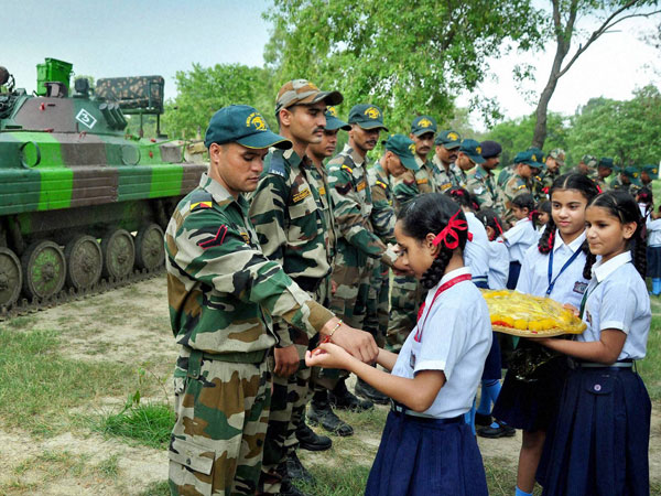 School girls tie rakhi on the wrists of Army soldiers