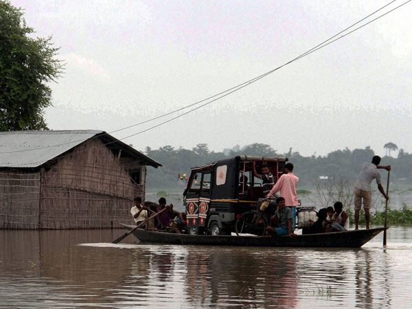 Villagers carry an auto rickshaw on a boat to safer areas