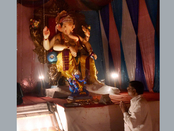 A devotee prays in front of an idol of Ganesh