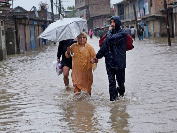 People wade through a street flooded due to incessant rains
