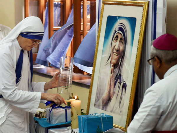 Lights a lamp in front of a portrait Mother Teresa on her death anniversary