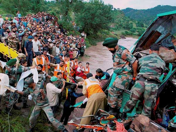Army soldiers and villagers recover the wreckage
