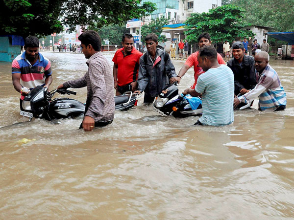 People pushing motorcycles stuck in a flooded locality