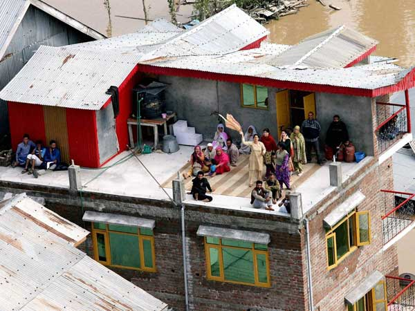 People stranded on a roof signalling IAF personnel