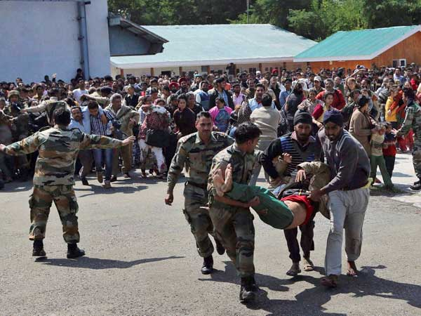 Indian army soldiers carry a seriously ill tourist