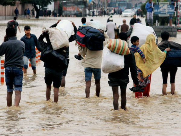 People carrying their belongings wade through a waterlogged street in Srinagar. (PTI Photo)