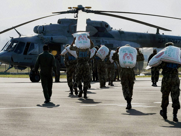 Army personnel load relief materials in a chopper