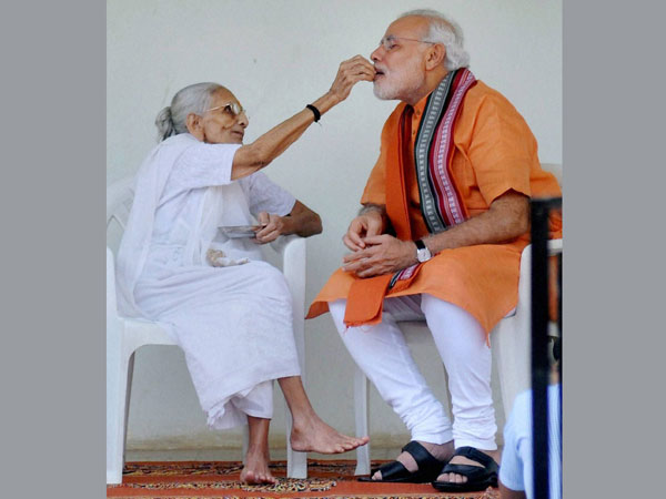 Prime Minister Narendra Modi is offered sweets by his mother